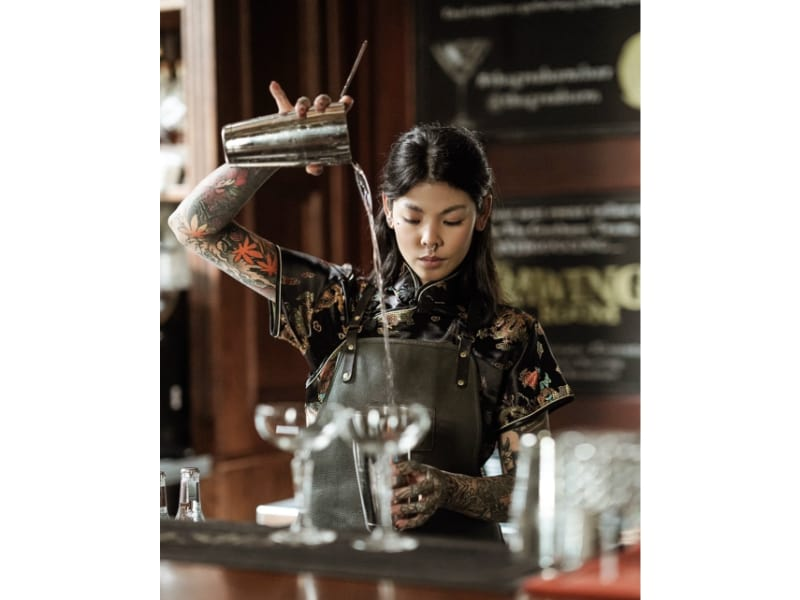 Millie Tang pouring liquor into a glass