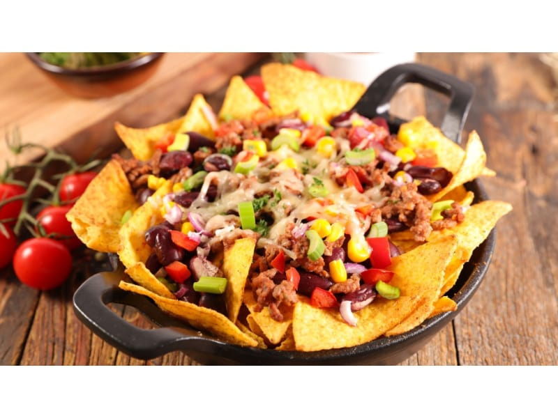 Nachos with beef, cheese, and vegetable toppings
