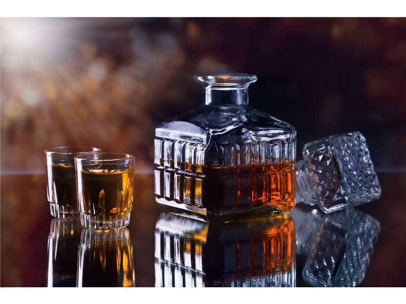 Open whiskey decanter with whiskey glasses