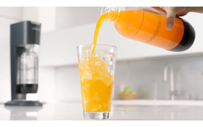 Orange drink being poured into a glass with a SodaStream machine at the back