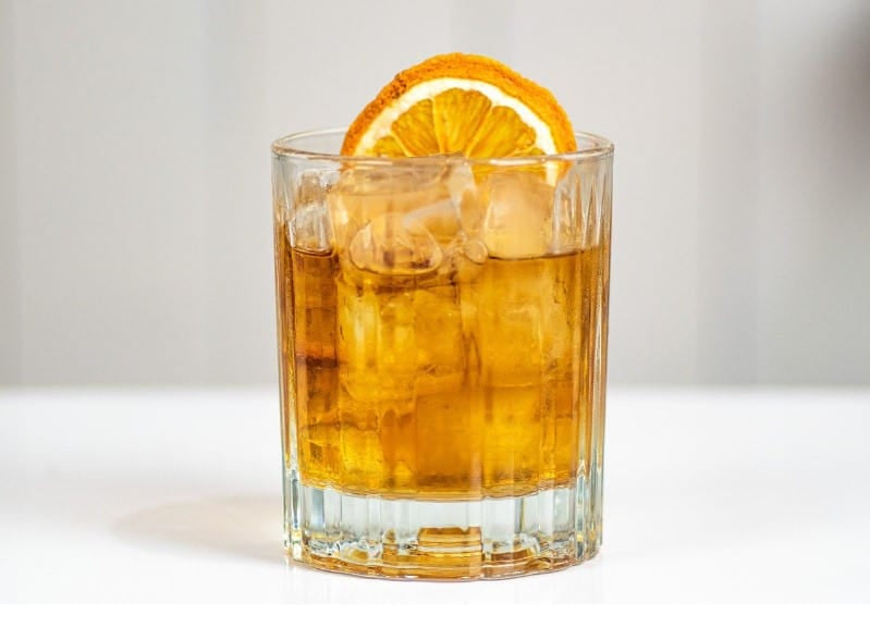 Orange Whiskey Cocktail in a glass, garnished with orange wedge