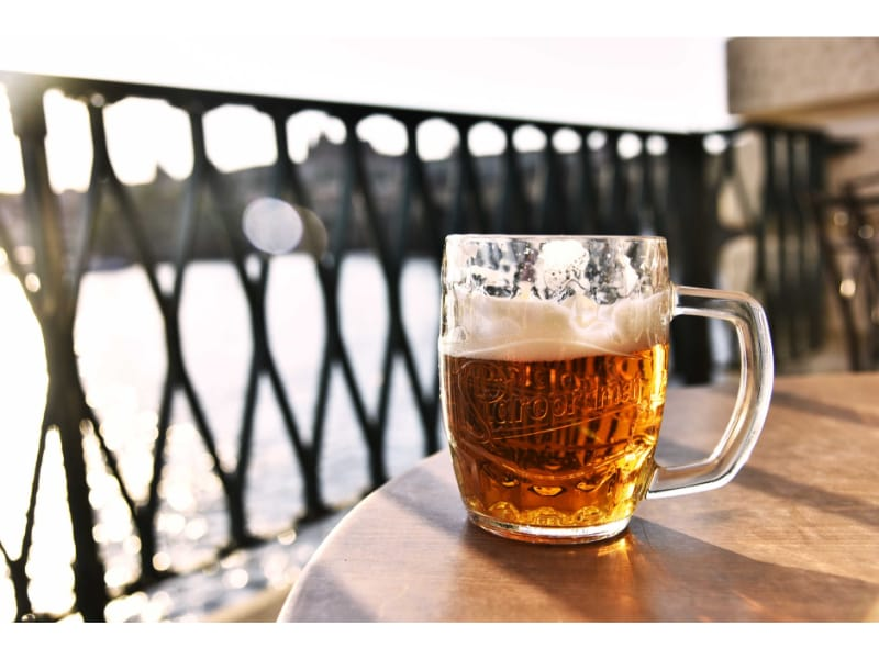 Mug of beer on top of a table in front if the sea