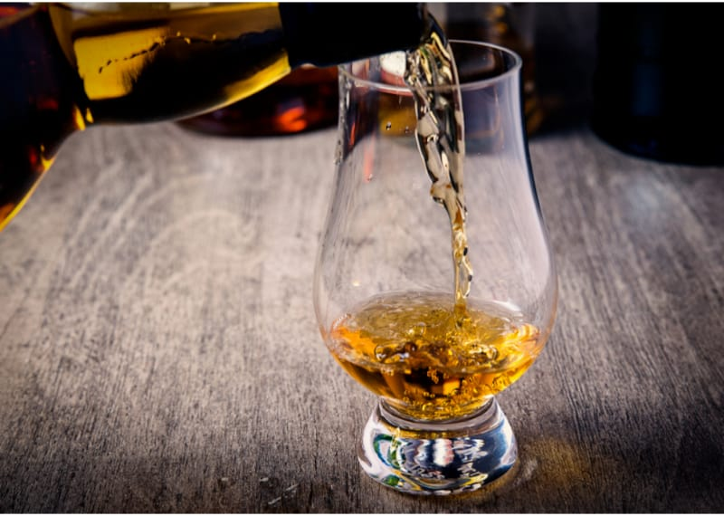 Pouring single malt scotch whisky into Glencairn whisky glass on wooden table