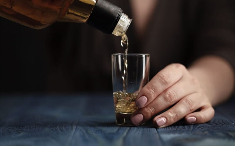 Pouring whiskey into glass shot
