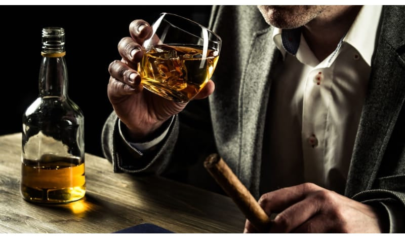 A man holding a glass of whiskey with tobacco on his finger