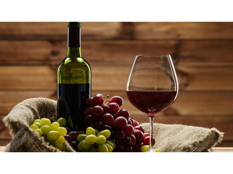 Red wine glass with bottle and grapes