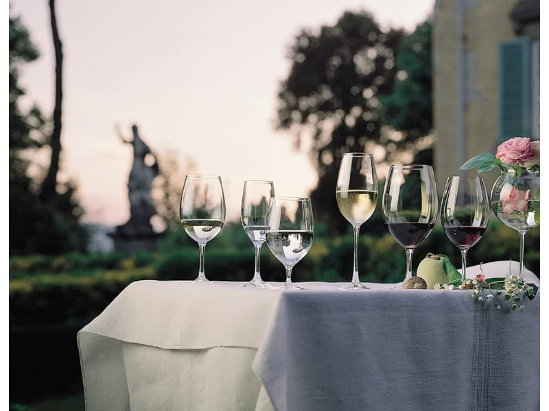 Various wine glasses on a table for an outdoor event.