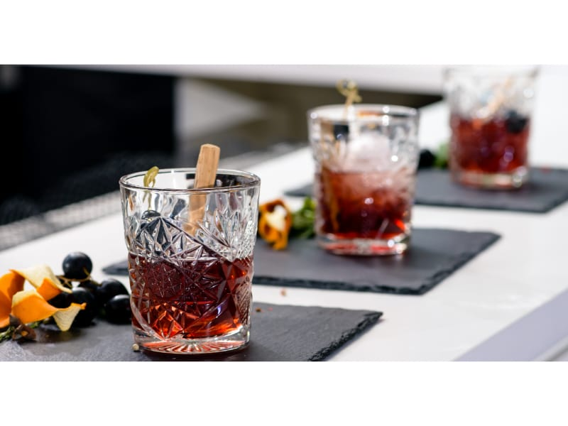 A tastefully designed rocks glass with premium whiskey and ice, served with fruits on the side.