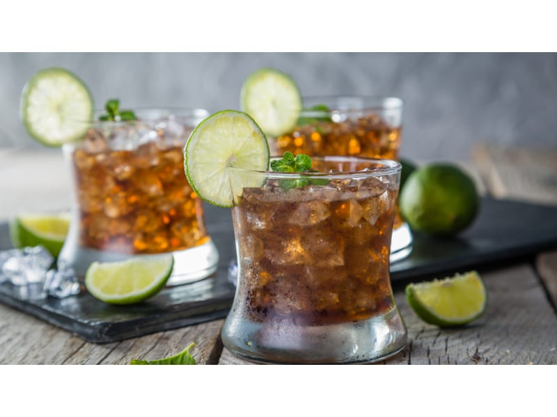 Rum cocktail with ice and lime wheel garnish