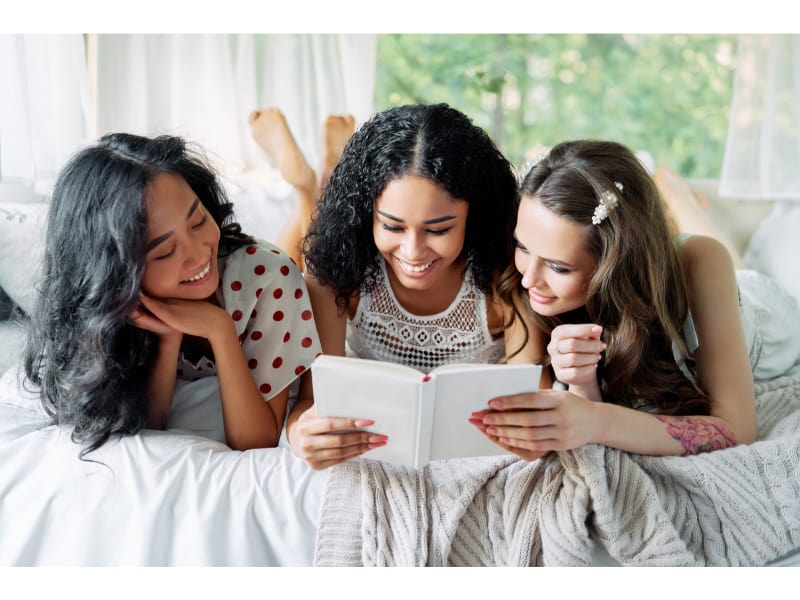 Smiling Multi Ethnic Girls Have Fun Together, Reading Book and E