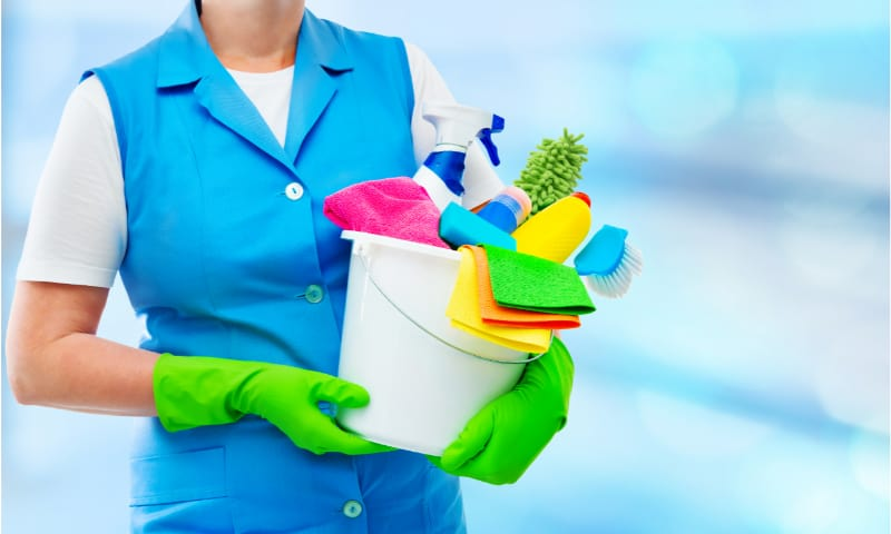 Woman carrying a bucket full of cleaning tools