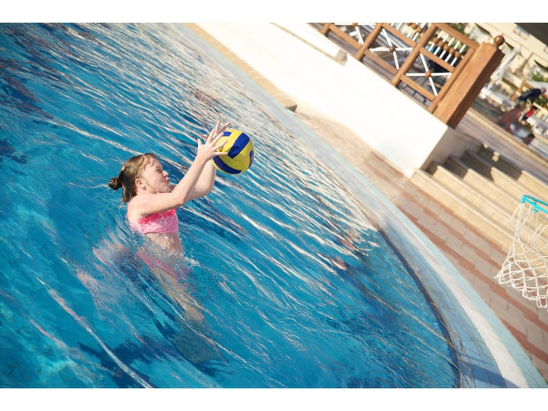 A girl in a swimsuit in a blue water pool throws a ball into a basketball