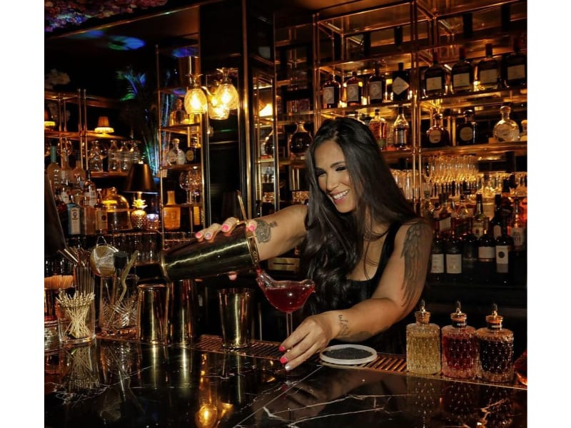 Shantal Edumar pouring a drink from a cocktail shaker