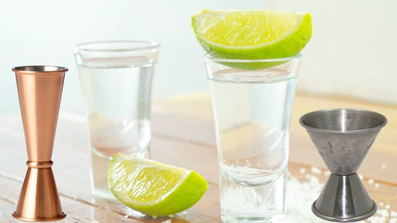 Shot glasses and jiggers with lime wedges