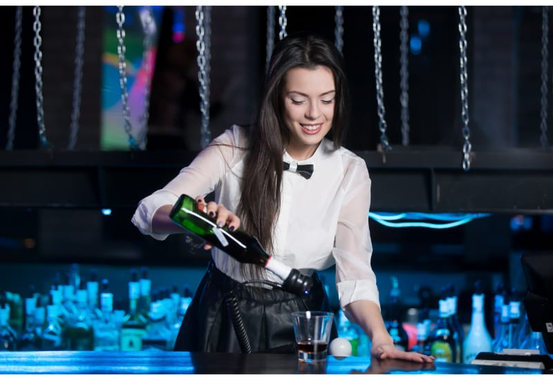 Woman pouring liquor on the glass behind the bar