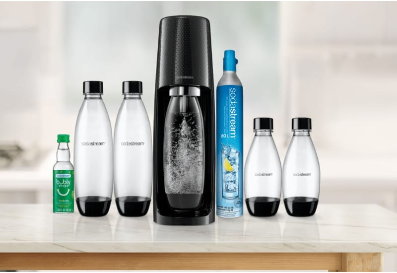 SodaStream machine with carbonating bottle on a kitchen counter