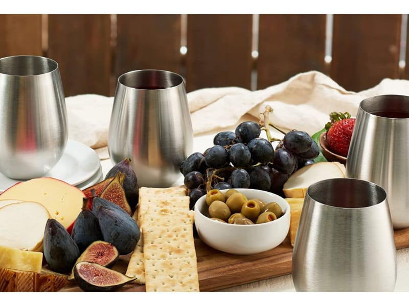 Stainless steel wine glasses with crackers and grapes picnic outdoors