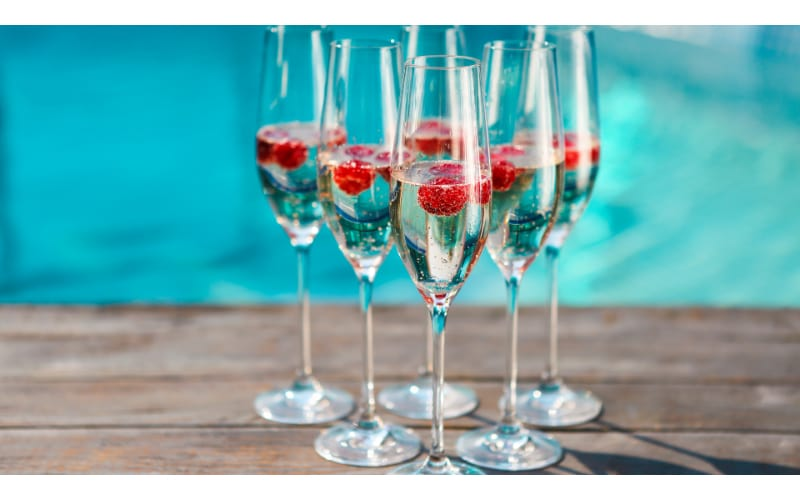 Champagne with raspberries in flute glasses by the pool.