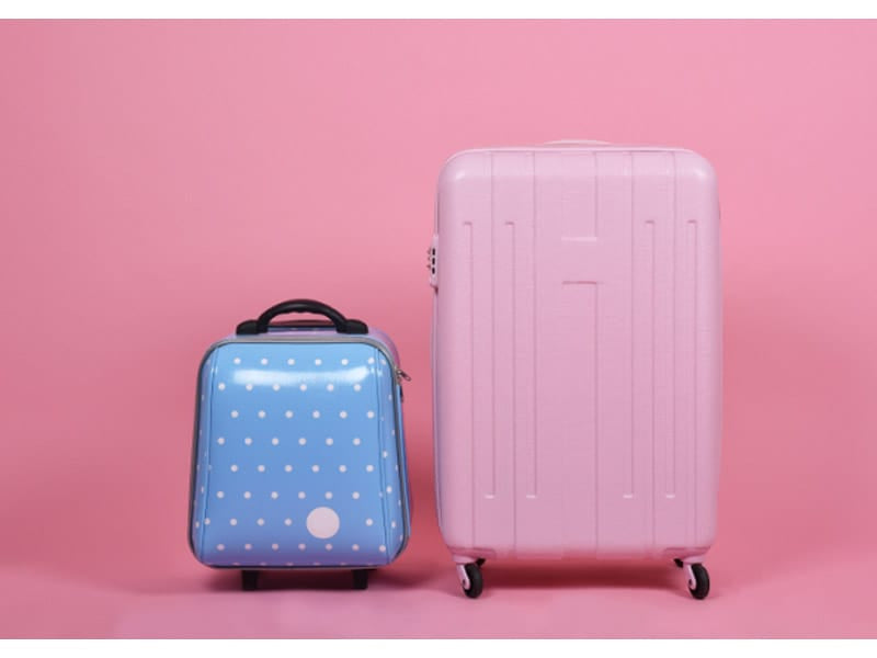 Small blue suitcase with a large pink suitcase