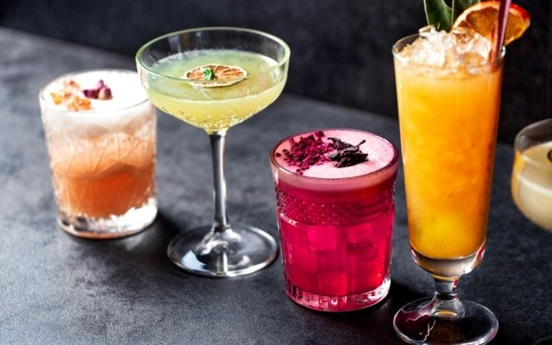 Tasty colored cocktails with various garnishes
