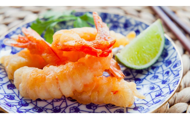 Tempura canapes served on a blue plate with a lime wedge on the side