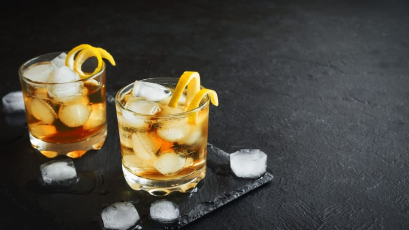 Two glasses of gold rum with lemon shavings and ice cubes