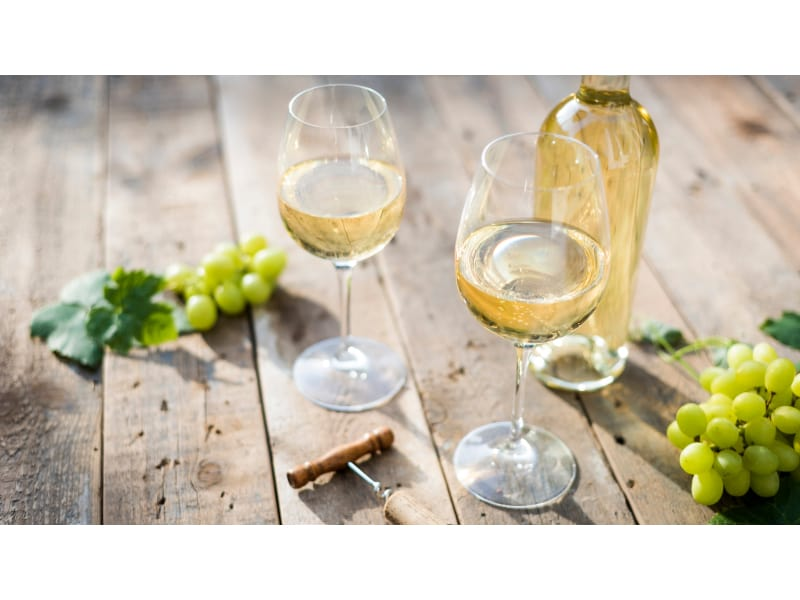 Two glasses of white wine with the bottle and grapes