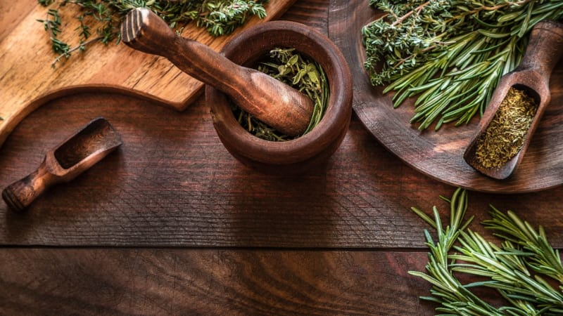 Various aromatic herbs with mortar and pestle