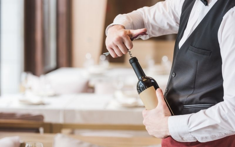 A waiter was captured on cam while uncorking a bottle of red wine.