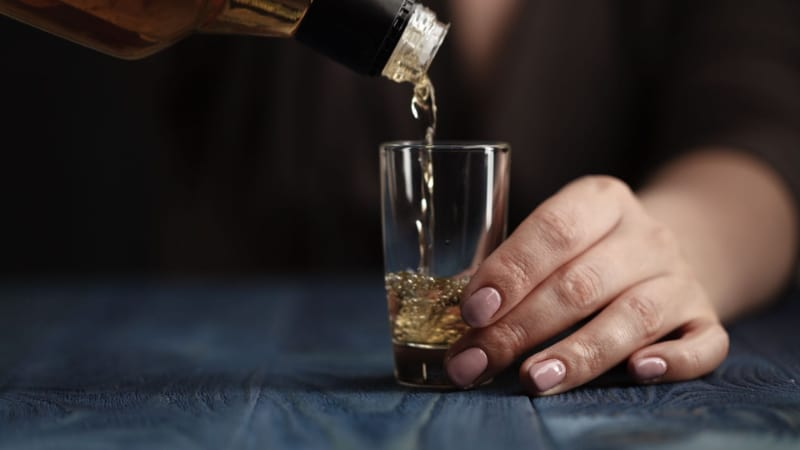 Whiskey being poured in a tall shot glass