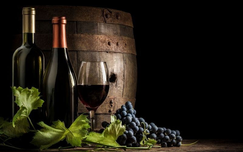 A wine barrel, two bottles of wine, and a glass of wine with grapes in the background