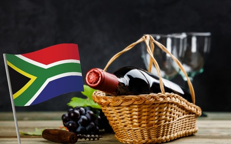 wine bottle in a basket, grapes, corkscrew with South Africa's flag