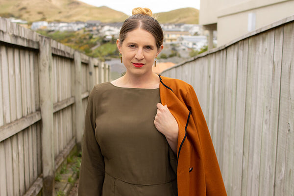 designer of Desiree Clothing wearing olive jumpsuit and rust coat