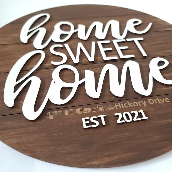 "Home sweet home laser cut round shiplap sign with engraved address and established year. Round shiplap painted brown with white script and print letters saying ""home sweet home"". White letters are attached on top of round shiplap creating a 3D element."
