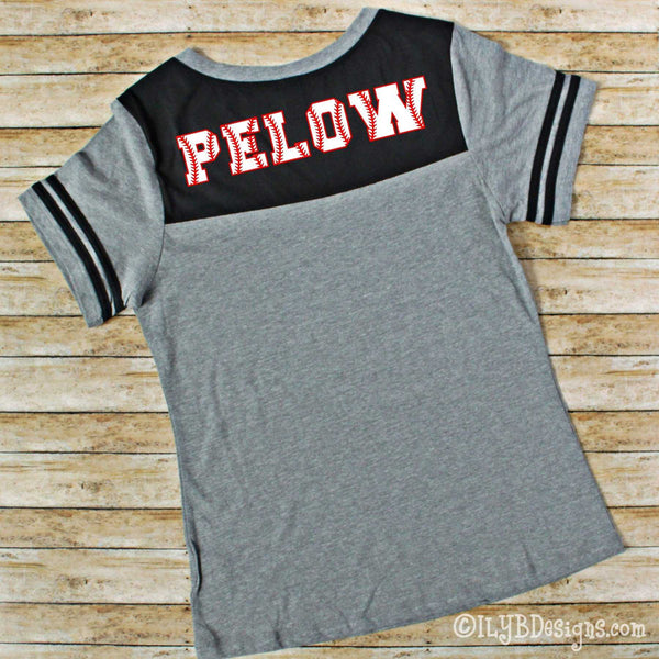 Back side of a medium heather gray bodied v-neck short sleeved shirt with 2 black stripes on each sleeve and black on the upper back of the shirt. A name appears on the black part of the shirt in collegiate style red and white letters that look like baseballs.