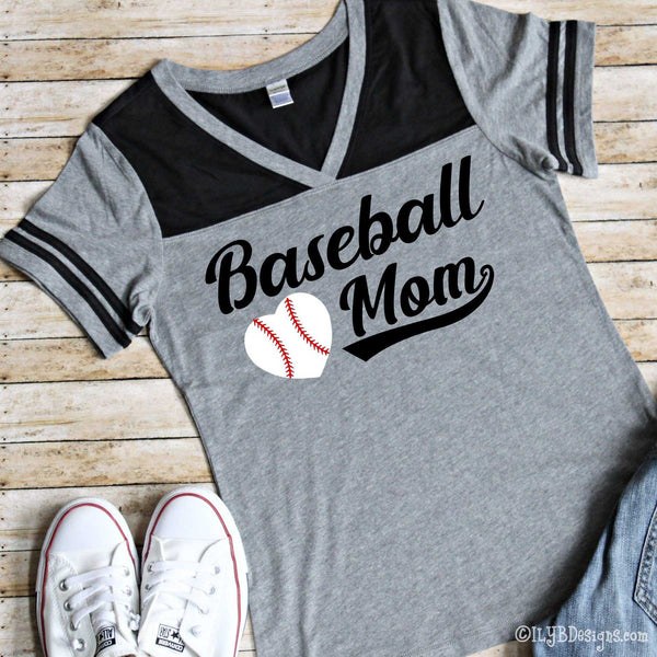 Baseball Mom in black sporty script with a swoosh underlining the word mom. A white heart with red baseball strings is placed to the left of the word mom and under the word baseball. Design is on a medium heather gray bodied v-neck short sleeved shirt with 2 black stripes on each sleeve and black on the upper chest of the shirt.