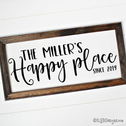 "Dark walnut stained 20""x10"" frame on a white canvas with black words in a mix of script and print fonts. It reads, ""The Miller's Happy place since 2019."" The design is placed horizontally on the sign."