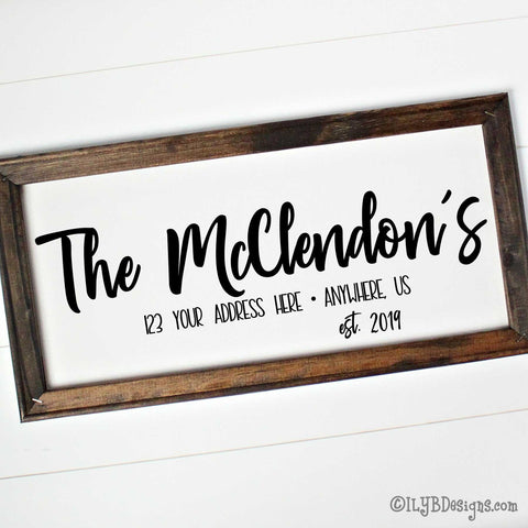 "Dark walnut stained frame on a white canvas with a black design. Design is placed horizontally on the 20""x10"" sign. Family name is in a bold script font with an optional address and established year underneath."