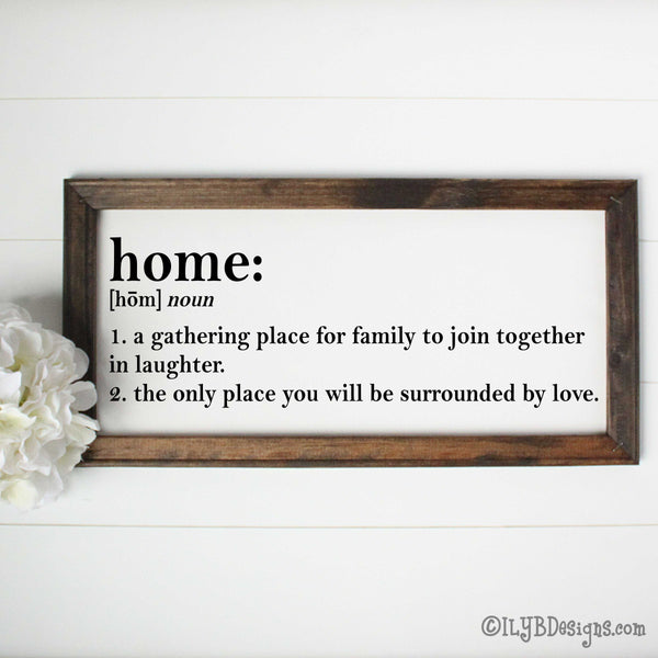 "Dark walnut stained 20""x10"" frame on a white canvas with black printed words that look like a dictionary definition.  It reads, ""home: noun, 1. a gathering place for family to join together in laughter. 2. the only place you will be surrounded by love."" Design is placed horizontally on the sign."
