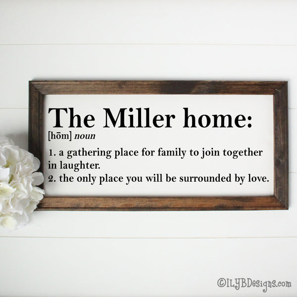 "Dark walnut stained 20""x10"" frame on a white canvas with black printed words that look like a dictionary definition.  It reads, ""The Miller home: noun, 1. a gathering place for family to join together in laughter. 2. the only place you will be surrounded by love."" Design is placed horizontally on the sign."