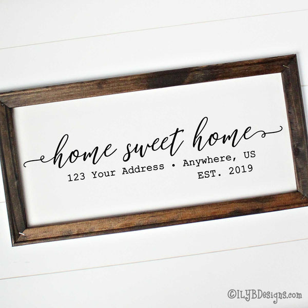 "Home sweet home written in black script with an optional address and established year below. Design is on a white canvas framed with a dark walnut stain frame. The frame measures 20""x10"" and design is placed horizontally."