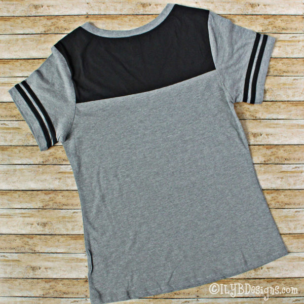 Back side of a medium heather gray bodied v-neck short sleeved shirt with 2 black stripes on each sleeve and black on the upper back of the shirt.