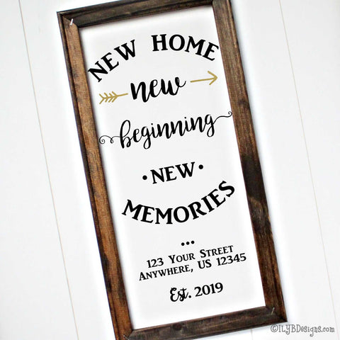 "Dark walnut stained frame on a white canvas with black wording in various fonts that says, ""New home, new beginning, new memories.""  A metallic gold arrow is split on each side of the first ""new."" Under the saying is the option to add an address and an established year."