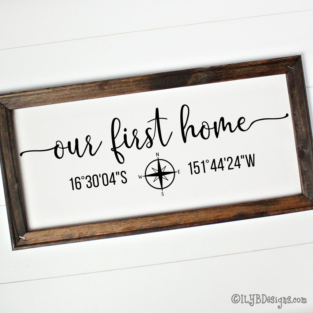 Our first home in a script font with a compass under the script and latitude and longitude coordinates on each side of the compass. Design is black on a white canvas and in a dark walnut stained wood frame.