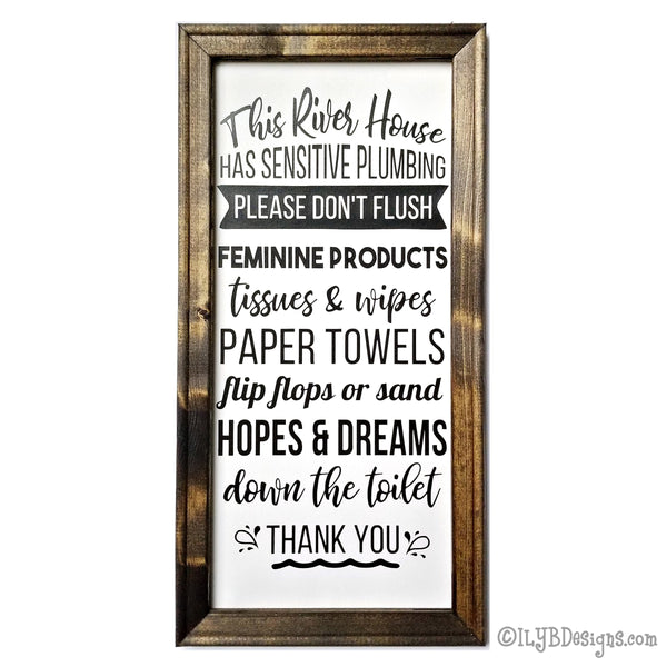 "Dark walnut stained frame on a white canvas with a black design. The design is word art in various decorative fonts saying: This river house has sensitive plumbing. Please don't flush feminine products, tissues and wipes, paper towels, flip flops or sand, hopes and dreams down the toilet. Thank you. Sign measures 10""x20"" and design is placed veritcally."