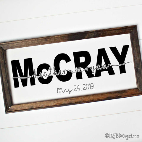 "A dark walnut stained 20""x10"" frame on a white canvas with a large, black last name in a bold print font. 2 first names in a silver gray script connected with an open heart are placed on the last name. An optional wedding date is below the name design in silver gray."