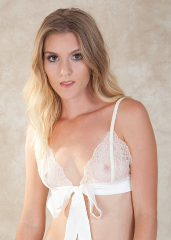 By Amoralle. The Adeline Bralette is made with delicate lace, satin and cream velvet straps. This luxurious bralette is a chic addition to any lingerie drawer. The statement bow is sure to awaken the grooms imagination. Complete the set with the matching Adeline Bikini. Available at Koki Intimi.