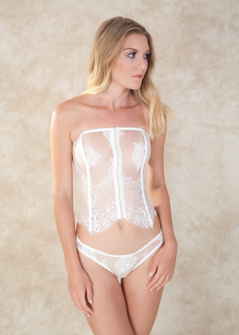 By Salua. The Angeletta Thong is made with sheer romantic lace on the front side, and a soft silk on the back, finished of with delicate picot elastic on the edges. This little white thong is simply a great wedding essential. To complete the bridal look pair with the Angeletta Corset. Available at Koki Intimi.
