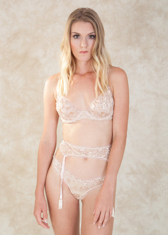 By Belle Et BonBon. The Nymph Floral Bra is a whimsical dream come true! Crafted with mesh and embellished with delicate petals, sequins and softly embroidered details. This beauty is framed with feminine semi-sheer light pink elastic. Complete the look with the  Nymph Floral Thong and Nymph Floral Garter Belt. Available at Koki Intimi.