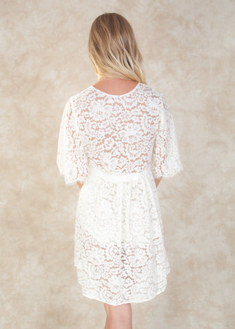 By Girl With A Serious Dream. The Elizabeth Robe is lovingly handmade from soft scalloped cotton lace with floral eyelash trims that go along neckline and the sleeves. Comes with an attached self-tie grosgrain belt to define the waist. Perfect for getting ready wedding photos! Available at Koki Intimi.